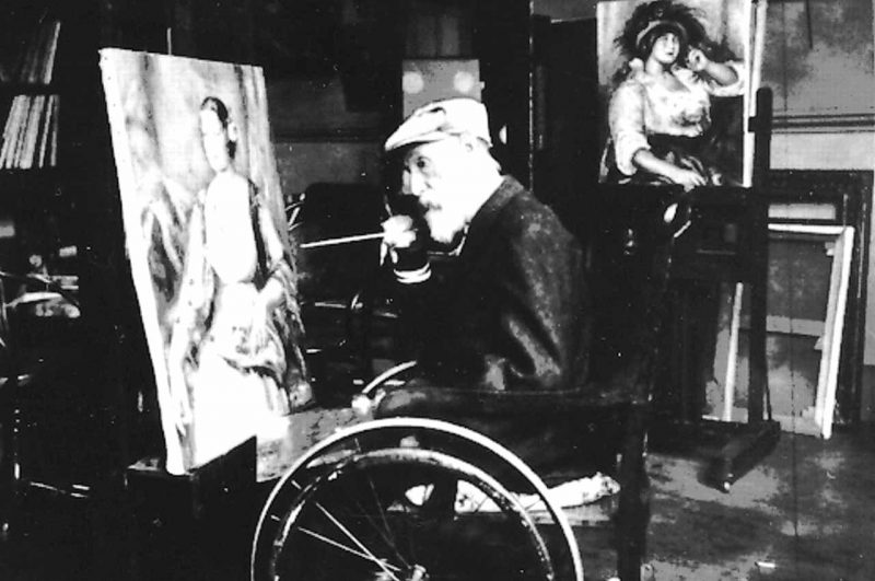 Renoir in wheelchair painting in his studio